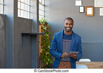 Smiling young African businessman using a tablet in an office