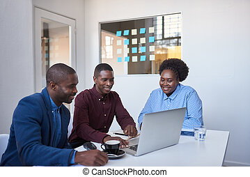 Smiling young African businesspeople using a laptop in an office