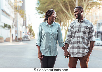 Smiling young African couple holding hands in the city together