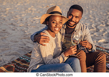 Smiling young African couple sitting at the beach drinking wine