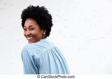 Smiling young african lady looking back