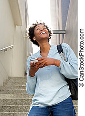 Smiling young african lady walking down the steps