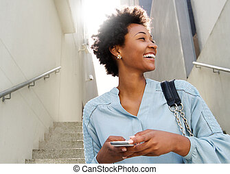 Smiling young african lady with mobile phone