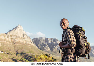 Smiling young African man enjoying the view while out hiking