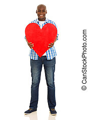 young african man holding heart shape - smiling young...