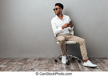 Smiling young african man sitting in a chair