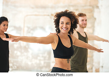 Smiling young african woman doing yoga exercises