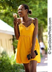 Smiling young african woman eating ice cream on outdoors