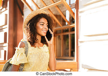 Smiling young african woman in summer dress