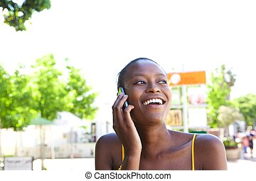 Smiling young african woman in the city talking on cellphone