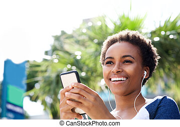 smiling young african woman listening to music with earphones