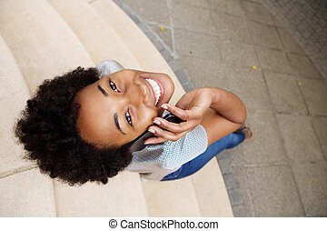 Smiling young african woman looking up and using mobile phone