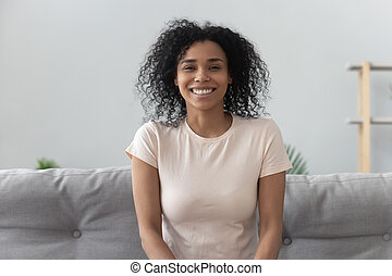 Smiling young african woman sit on sofa looking at camera