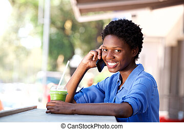 smiling young african woman sitting at cafe and making phone call