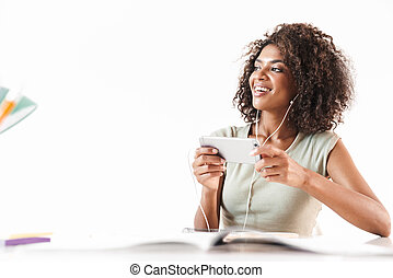 Smiling young african woman sitting at the desk