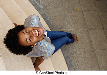 Smiling young african woman sitting on steps and looking up