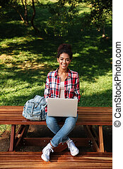 Smiling young african woman sitting outdoors in park