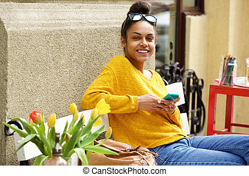 Smiling young african woman sitting outside