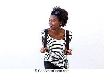 Smiling young african woman standing against white wall and looking away