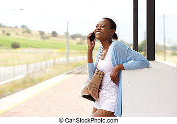 Smiling young african woman standing with cell phone and bag