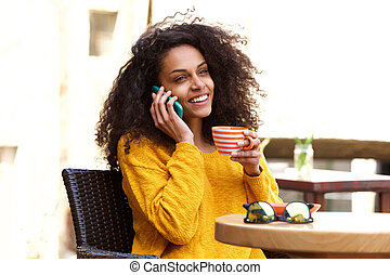 Smiling young african woman talking on cellphone at cafe