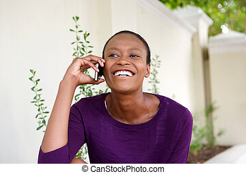 Smiling young african woman talking on mobile phone
