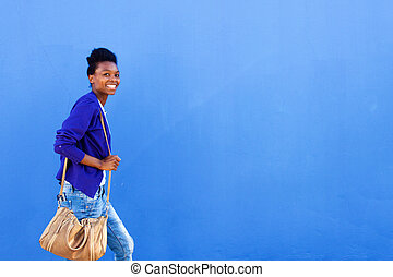 Smiling young african woman walking against blue wall