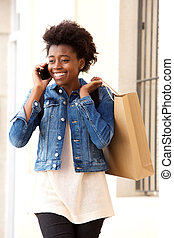 Smiling young american woman talking on mobile phone with shopping bag