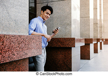 Smiling Young Asain Businessman Using Mobile Phone in the City. Looking at the Camera