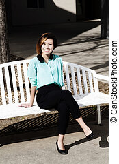 Smiling Young Asian American Woman Sitting On Bench Outdoors