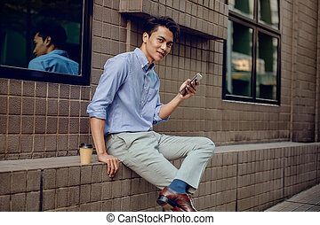 Smiling Young Asian Businessman Using Mobile Phone in the City. Looking at the Camera