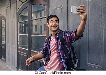 752f7d5a6 Happy asian man sending a text on his cellphone outside. Square ...