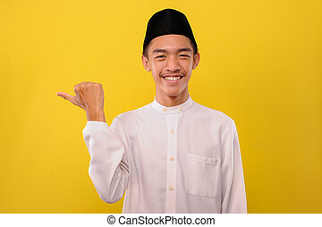 Smiling Young Asian muslim man showing a copy space to presenting something