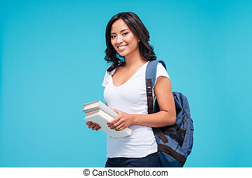 Smiling young asian student girl standing with books