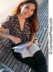 Smiling young Asian university student studying on a campus bench