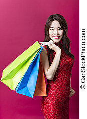 smiling young asian woman holding the shopping bags