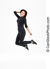 Smiling young asian woman jumping