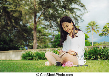 Smiling young Asian woman sitting on the grass in a park while writing on diary.