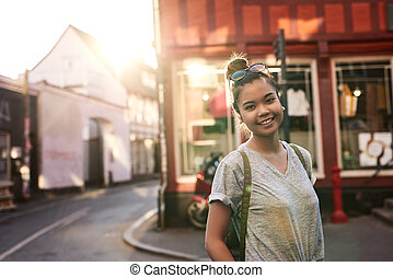 Smiling young Asian woman spending an afternoon in the city