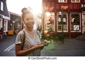 Smiling young Asian woman using her cellphone in the city