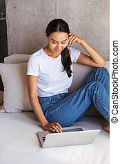 Smiling young asian woman using laptop computer
