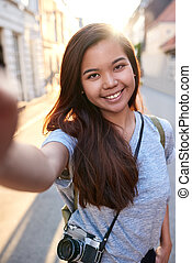 Smiling young Asian woman walking in the city taking selfies