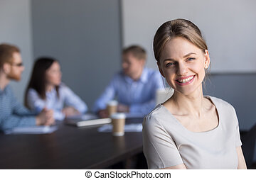 Smiling young attractive professional businesswoman looking at c