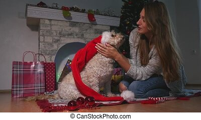 Smiling young attractive woman embracing cute puppy dog in Christmas hat