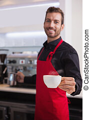 Smiling young barista holding jug and cup of coffee