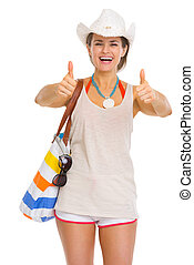 Smiling young beach woman in hat showing thumbs up