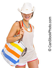 Smiling young beach woman with hat pulled over eyes