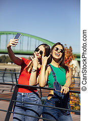 Smiling young best female friends taking selfie in the park