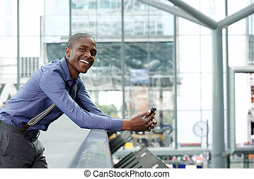 smiling young black businessman with cellphone