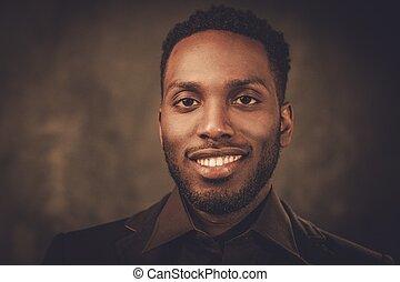 Smiling young black man posing on dark background.